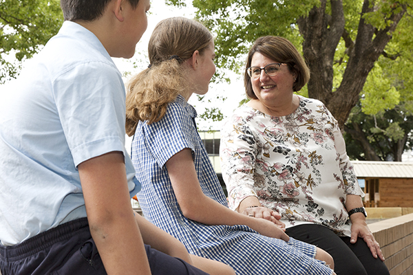 St Pius Catholic Primary School Enmore - students sitting and talking to the Principal