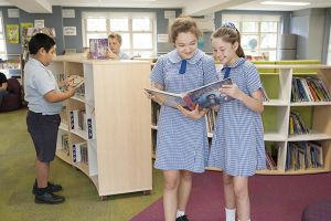St Pius Catholic Primary School Enmore - students looking at books in the library